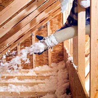 An insulation contractor spraying in insulation.